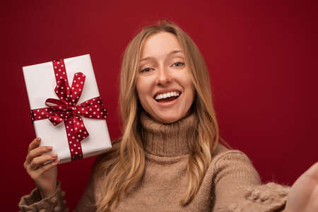 Image of charming young blonde woman in warm sweater smiling and holding gift with red ribbon. Studio shot red background. New Year Women's Day birthday holiday concept