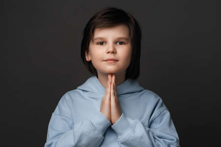 Portrait of boy 10-12 years old in casual clothes keeping palms together and praying. He meditating, praying for peace and love, having calm and peaceful facial expression. Facial expression concept