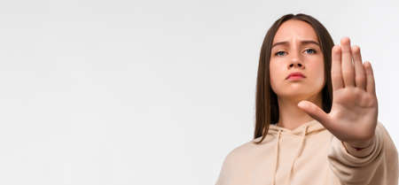 Young pretty woman with long chestnut hair, looking serious and stern, wearing casual beige hoodie, showing open palm making stop gesture. Copy space for your text