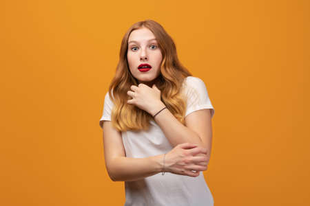 I'm afraid. Fright, phobia, panic attack, horror. Portrait of the scared girl with wavy redhead, wearing white t-shirt, isolated on yellow background