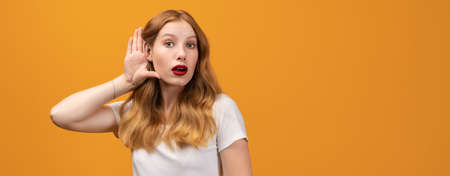 Young pretty woman with wavy redhead, wearing white t-shirt holding hand near ear trying to listen something, isolated over yellow background. Copy space for your text