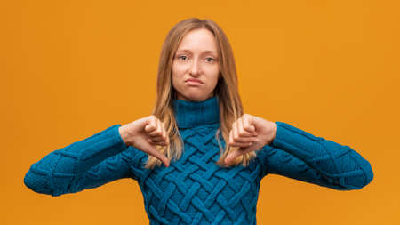 Unhappy Young woman in knitted blue sweater showing a thumbs down. Unlike, dislike, failure gestures concept, body language. Studio shot, yellow background, isolated