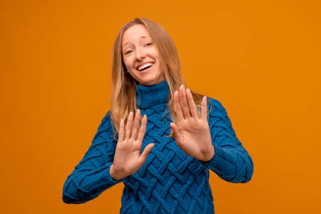Portrait of embarrassed young woman in knitted blue sweater looking at camera. Studio shot, yellow background, isolated. Human emotions, facial expression concept Archivio Fotografico