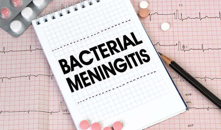 Notebook page with words - Bacterial Meningitis nearby with a pills and pencil, medical concept, top view Archivio Fotografico