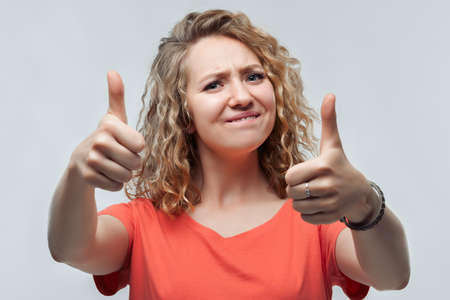 Portrait of cheerful blonde girl with curly hair in casual t shirt showing thumbs up. I like that. Good job. Studio shot, white background. Human emotions concept
