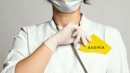 Cropped view of doctor in a white coat and sterile gloves holding a note with word - ANEMIA. Medical concept