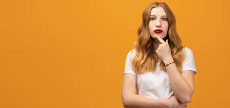 Photo of Pensive young woman with wavy redhead standing with hand raised on chin and looking thoughtfully into a camera isolated over yellow background. Concept of thinking. Copy space for your text Standard-Bild