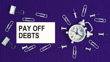 Pay off debts - concept of text on business card. Closeup of a personal agenda