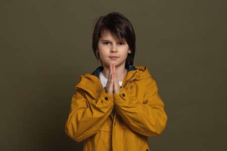 Cute little boy 11-13 years old keeps palms pressed together having regretful look, asking for forgiveness. Forgive me please. Studio shot, green background Standard-Bild