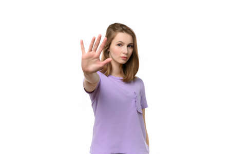 Portrait of a serious girl standing with outstretched hand showing stop gesture, refuse offer. Human emotions and feelings, facial expression concept Stock fotó