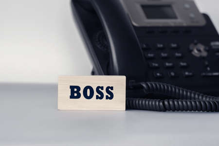 Closeup of the wooden block with text - BOSS. Office and communication concept
