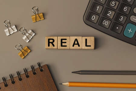 Word - REAL - on small wooden blocks on the desk. Conceptual photo. Top view