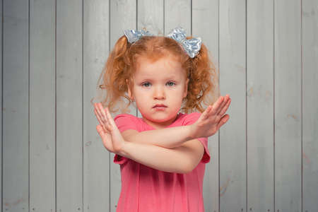 serious redhead preschooler girl holding two arms crossed, say no, stop gesture, warning of end finish, forbidden way. Studio shot, light wooden background Stock fotó