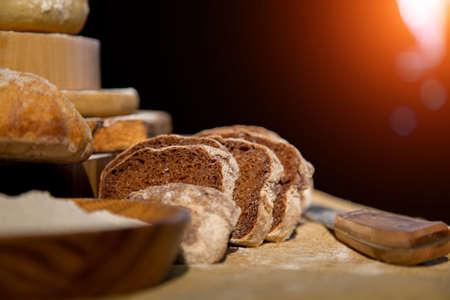Pan fresco de centeno y harina de trigo sobre la mesa. Composición de un conjunto de pan sobre un fondo oscuro. Panadería.