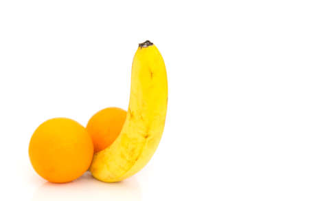 One banana and two orange fruts isolated on white background. Concept - male potency. Imagens
