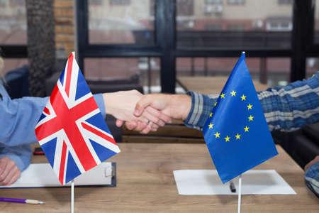 Nahaufnahme der Flaggen der Europäischen Union und Großbritanniens vor dem Hintergrund eines Händedrucks. Partnerschaftskonzept.
