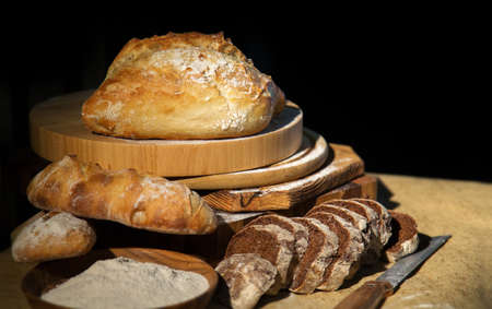 Fresh bread from rye and wheat flour on the table. Composition from a set of bread on a dark background. Bakery. Stock Photo