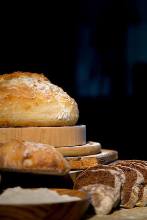 Fresh bread from rye and wheat flour on the table. Composition from a set of bread on a dark background. Bakery. 免版税图像