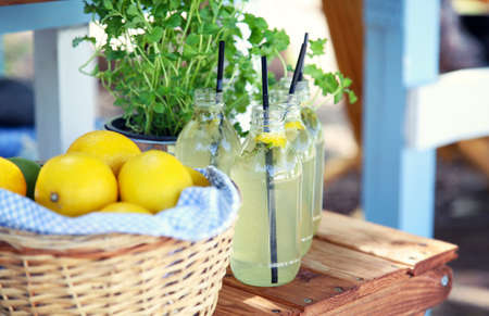 Fresh lemonade and a basket with lemons on a wooden table on a summer hot day.