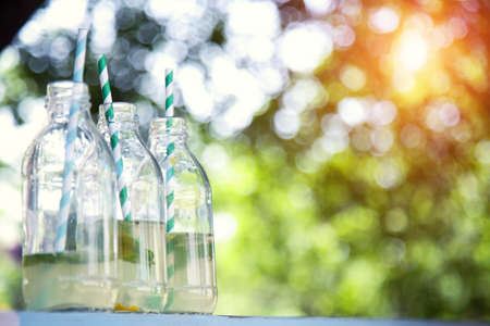Bottles of fresh lemonade on the background of natural bokeh.