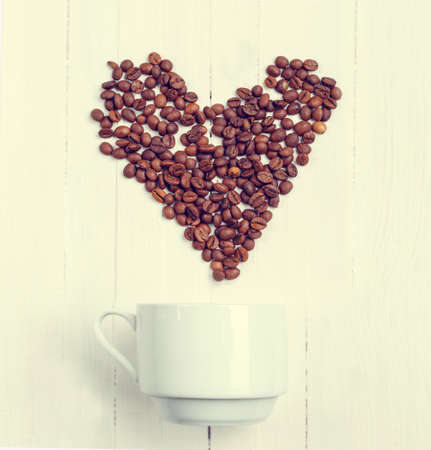Love coffee. Grain of coffee in the form of a heart over a cup. Top view. Postcard. Flat lay image.