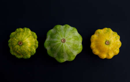 Three pattypan squash vegetable. Group of green and yellow squashes, on dark background.