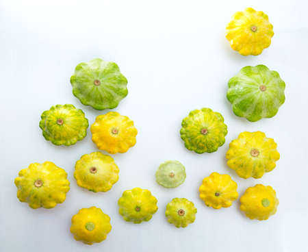 Pattypan squashes vegetable. Group of green and yellow pattypan squashes, on white table background.