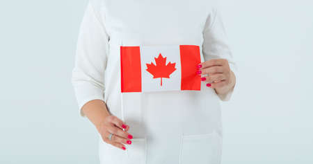 Close-up of the flag of Canada in female hands. Woman is Canadian.