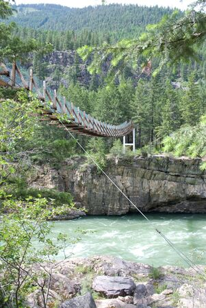 Swinging bridge over a mountain river Stock Photo