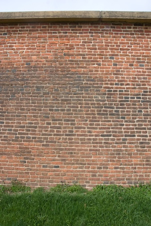 Brick wall with grass in front of it. Banco de Imagens