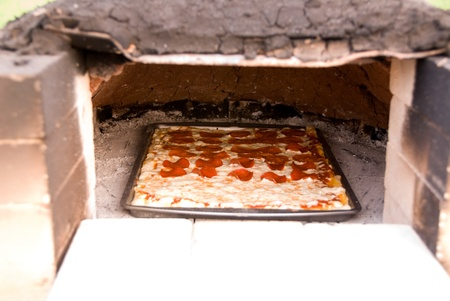 Pepperoni pizza cooking in earthen oven