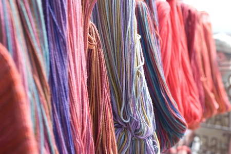 Skeins of colorful yarn hanging, shallow DOF