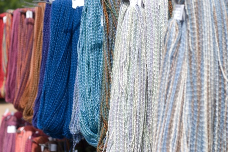 Skeins of colorful yarn hanging, grays and blues
