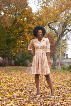 americal: Young adult african americal lady with big grin looking at camera on walkway covered with leaves Stock Photo