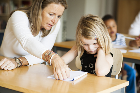 uninterested: Teacher teaching to bored girl in classroom LANG_EVOIMAGES