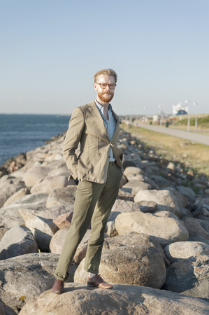 formals: Portrait of businessman standing on rocks at beach