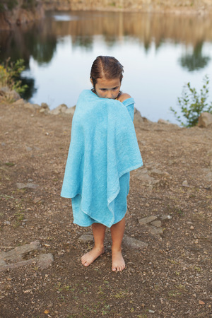 Full length of girl wrapped in towel standing at lakeshore