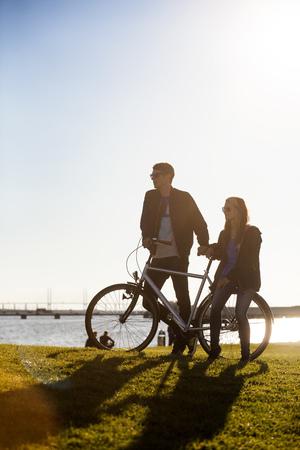 niño parado: Pareja con bicicleta en el parque por mar contra el cielo claro LANG_EVOIMAGES