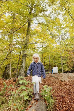 Girl walking on log in park LANG_EVOIMAGES