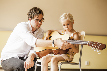 Male teacher teaching girl to play guitar LANG_EVOIMAGES