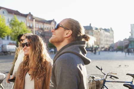 incidental people: Happy couple looking away while standing on city street