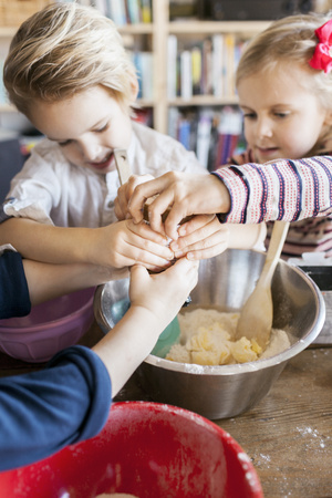 Siblings adding ingredient in dough while baking at home
