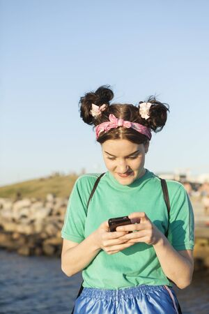 Young woman using mobile phone at shore