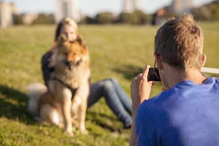 Rear view of man photographing girlfriend and dog at park