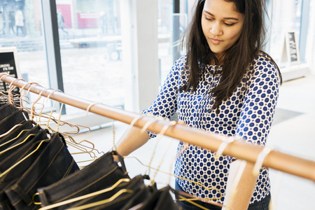 purchasers: Confused woman choosing jeans in factory