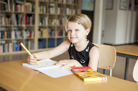 primary product: Portrait of cute girl drawing with color pencil in classroom