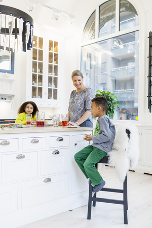kitchen island: Happy mother with children having breakfast at kitchen island LANG_EVOIMAGES