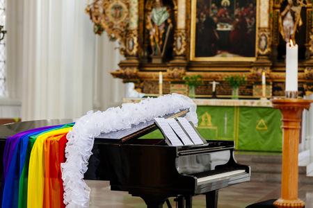 boas: Boa and gay pride flag on grand piano in church