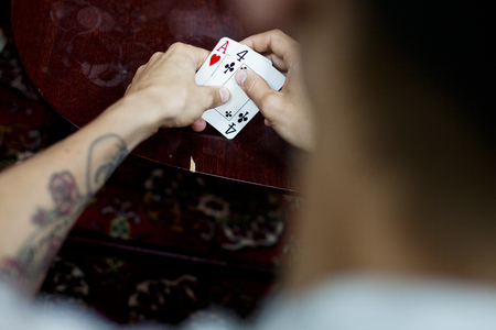 hope indoors luck: Cropped image of man playing cards at home