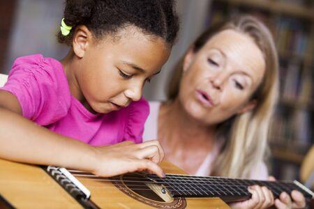 Female teacher teaching girl to play guitar